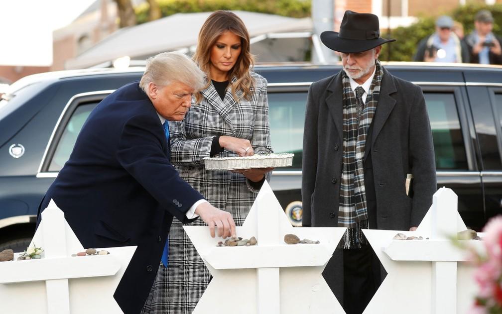 O presidente dos EUA, Donald Trump, deposita uma pedra em homenagem a vítimas de massacre em memorial na Sinagoga Árvore da Vida, acompanhado pela primeira-dama, Melania, e pelo rabino Jeffrey Myers, em Pittsburgh, em 30 de outubro — Foto: Reuters/Kevin Lamarque