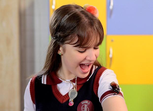 Poliana (Sophia Valverde) fica aflita com uma barata em sua roupa (Foto: Lourival Ribeiro, Gabriel Cardoso/ SBT)