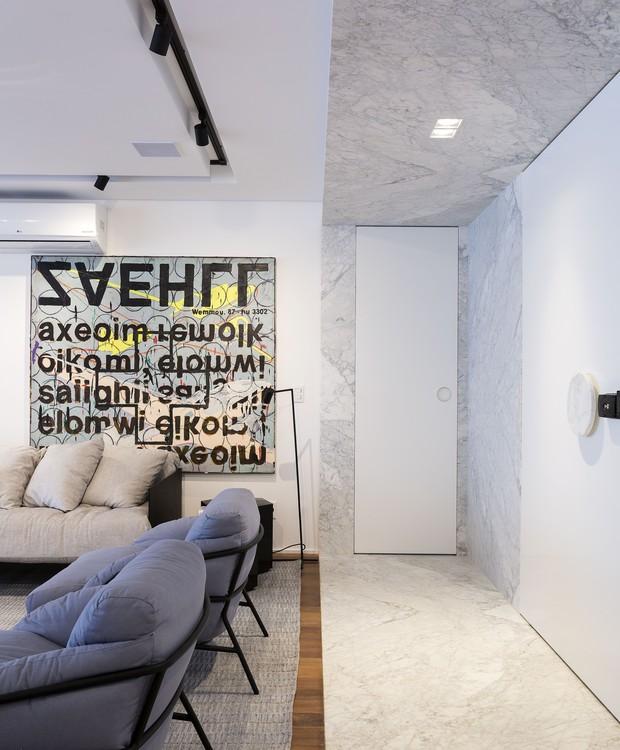 O hall revestido de mármore guarda as passagens para o lavabo e a área íntima. A tela de Guilherme Callegari é uma das obras de arte que enfeitam o apartamento (Foto: Marcelo Ribeiro/Divulgação)