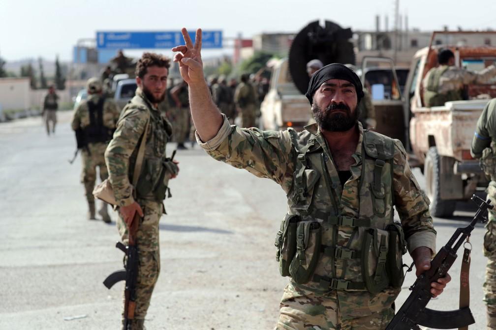 Um militar rebelde da Síria, de um grupo apoiado pela Turquia, acena na cidade Tel Abyad, na fronteira entre os dois países, em 14 de outubro de 2019 — Foto: Khalil Ashawi/Reuters
