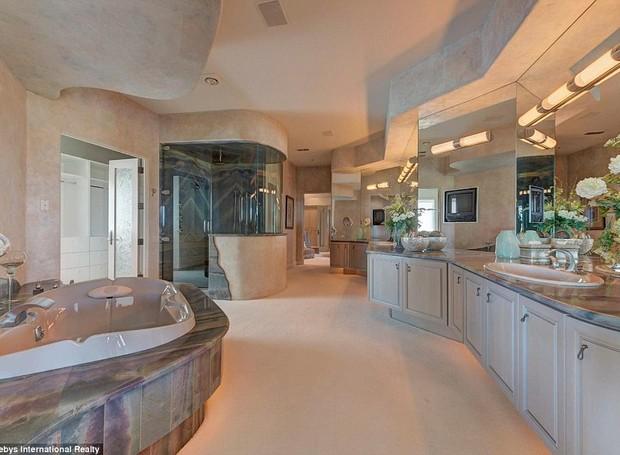 O banheiro da suíte principal é espaçoso e possui os móveis claros