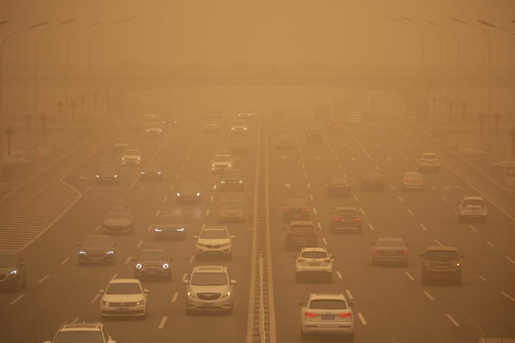 Veículos em via expressa de Pequim em meio a tempestade de areia que derrubou a qualidade do ar da capital chinesa — Foto: Mark Schiefelbein/AP