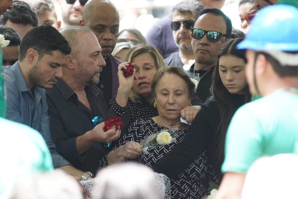 Mãe de Gugu, Maria do Céu, leva rosa branca para se despedir do filho. — Foto: Marcelo Brandt/G1