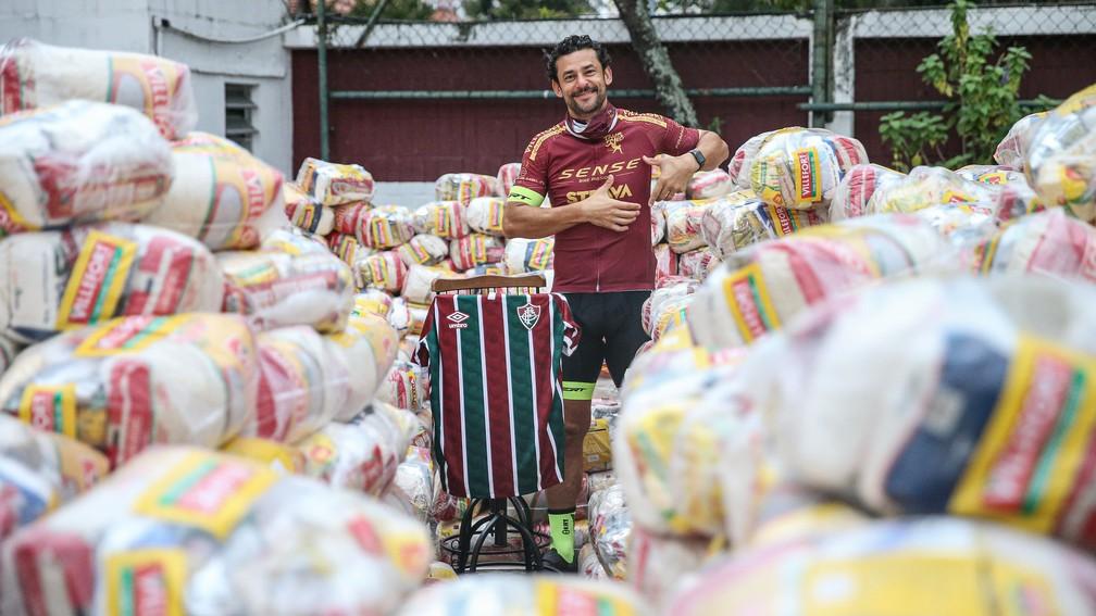Fred posa com as cestas básicas doadas e com a camisa do Fluminense — Foto: Lucas Merçon / FFC