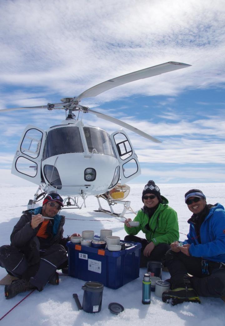 Daisuke Hirano (centro) com um piloto de helicóptero (esquerda) e um assistente de campo (direita) almoçando na geleira Shirase (Foto: Yuichi Aoyama)