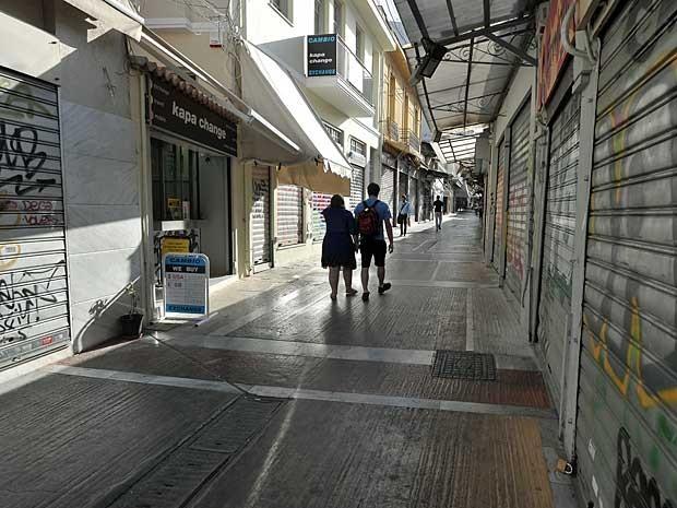 Casal anda por região de comércio em Atenas, cujas lojas não abriram nesta quinta-feira (18). (Foto: Louisa Gouliamaki / AFP Photo)