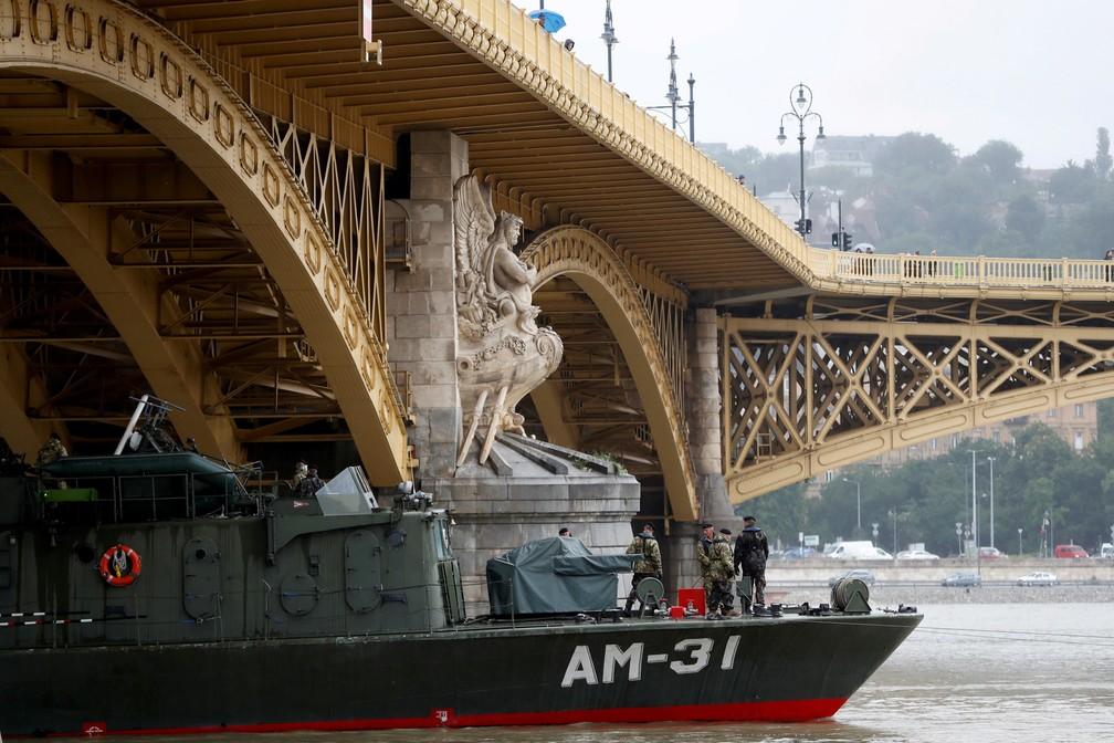 29 de maio - Um barco do exército húngaro passa sob a ponte de Margaret, em Budapeste, após o naufrágio de um barco de turismo matar 7 pessoas no rio Danúbio. Outras 21 pessoas ainda estão desaparecidas — Foto: Bernadett Szabo/Reuters