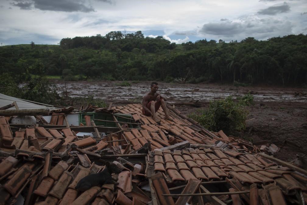 Emerson dos Santos, 30, senta no telhado de casa para proteger o que restou dos pertences da família de saqueadores, em área atingida pela lama por conta do rompimento da barragem da Vale, em Brumadinho. — Foto: Mauro Pimentel/AFP