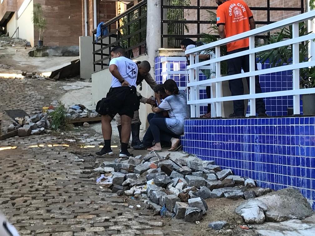 Homem é abraçado pela neta após ser resgatado em área onde prédios desabaram no RJ — Foto: Raísa Pires/G1