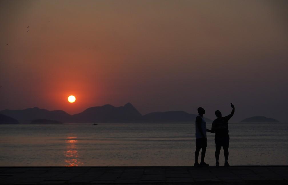 Homens fazem selfie durante o nascer do sol na Praia Vermelha — Foto: Marcos Serra Lima/G1