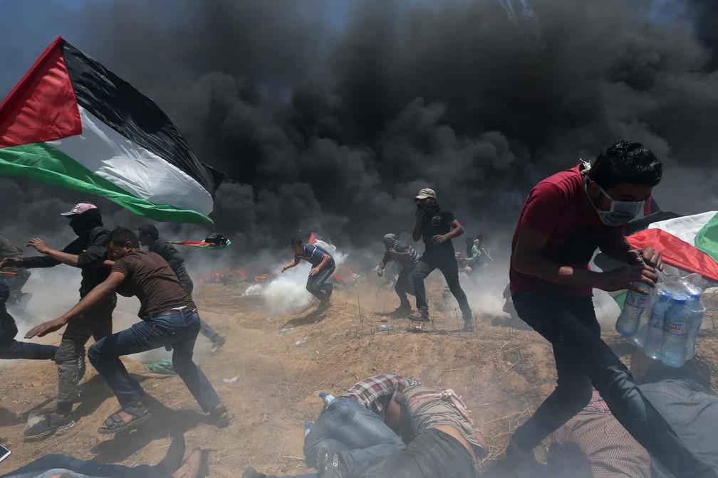 Manifestantes palestinos correm para se proteger de tiros e bombas de gás atiradas por tropas israelenses durante protesto na fronteira entre Israel e Gaza contra a inauguração de embaixada dos EUA em Jerusalém (Foto: Ibraheem Abu Mustafa/Reuters)