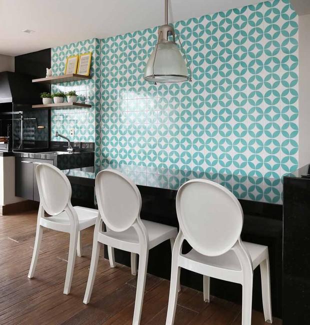 VARANDA | O pendente, a mesa e as cadeiras são acervo pessoal da moradora. Os objetos decorativos nas prateleiras, ao lado da churrasqueira, são da Zacche Home. (Foto: Mariana Orsi/ Divulgação)