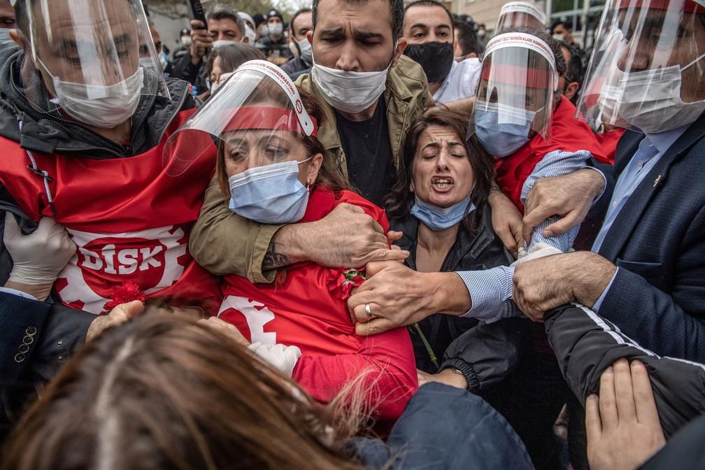 Manifestantes com máscaras de proteção lutam com a polícia turca durante comício no Dia Internacional do Trabalho, em Istambul. A polícia de Istambul deteve vários manifestantes que tentaram marchar em direção à simbólica Praça Taksim de Istambul, desafiando o bloqueio imposto pelo governo devido ao surto de coronavírus — Foto: Bulent Kilic/AFP