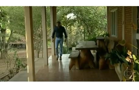 Caio na varanda de sua casa, que tem móveis rústicos de madeira maciça Reprodução
