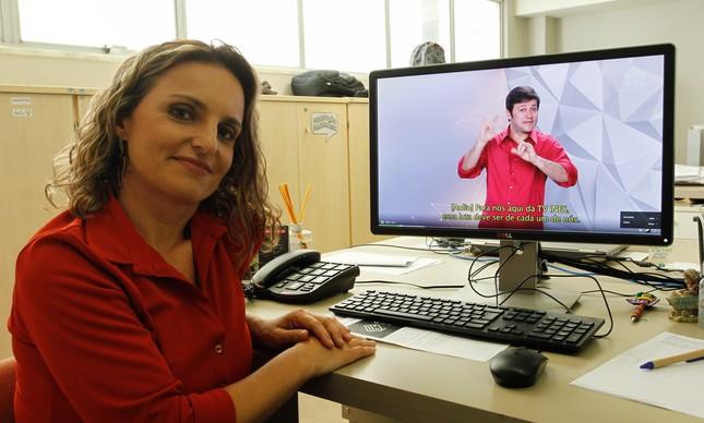 """Roteirista do """"Primeira Mão"""", a jornalista Roberta Savedra junto a uma tela que mostra o programa"""