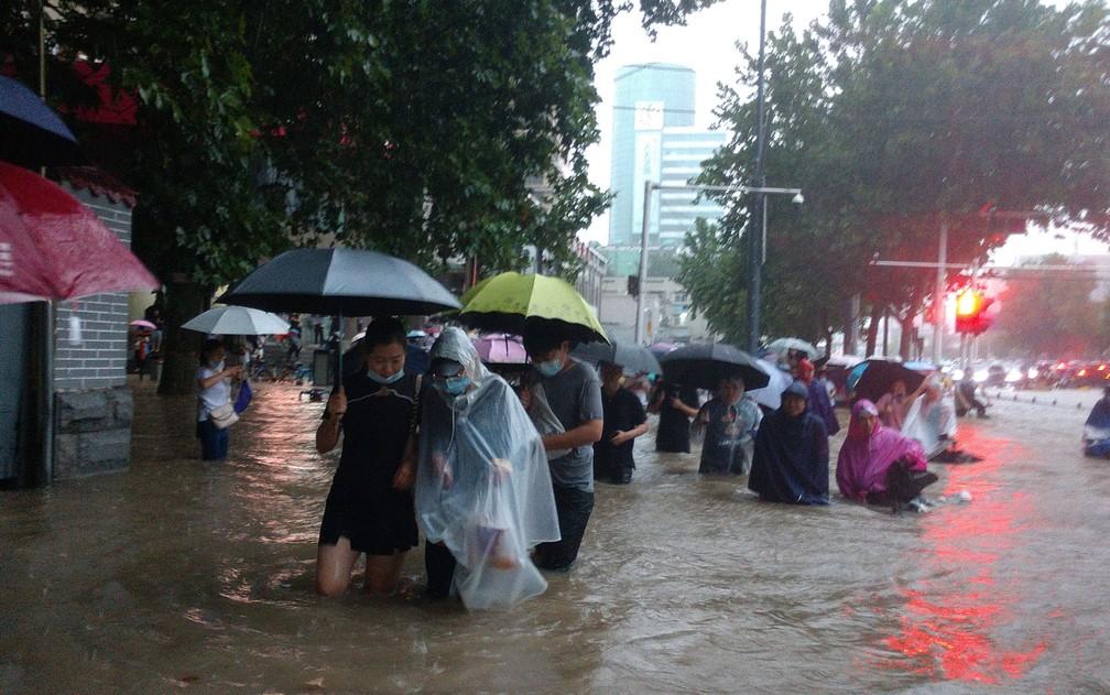 Pessoas tentam atravessar ruas alagadas após forte chuva em Zhengzhou, capital da província de Henan, na China, na terça-feira (20) — Foto: Chinatopix via AP