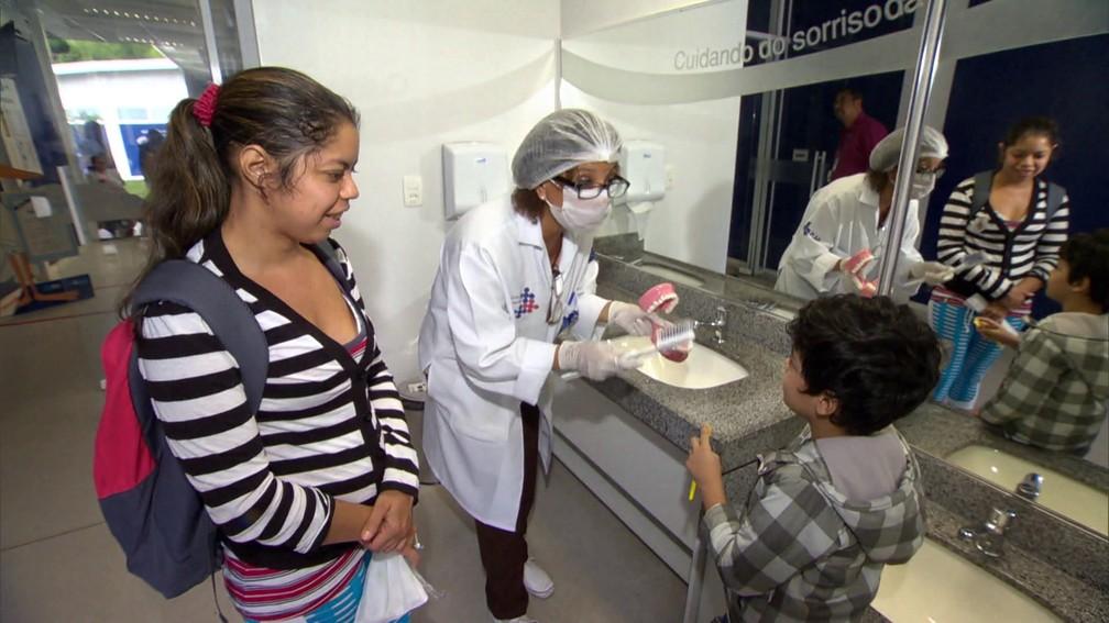 Criança recebe instrução para escovar os dentes na rede pública de saúde no Brasil; país fornece acesso universal à saúde  (Foto: Rede Globo)