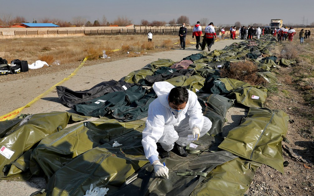 Investigador forense trabalha no local da queda de avião ucraniano no Irã em meio a corpos nesta quarta-feira (8) — Foto: AP Photo/Ebrahim Noroozi