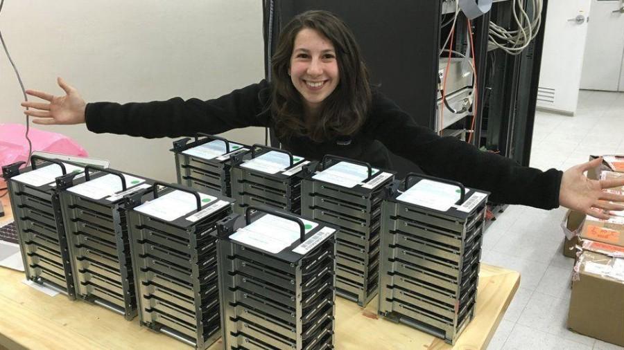 Katie Boumnan ao lado do código que tornou possível avistar a primeira imagem de um buraco negro (Foto: Reprodução/ Facebook)