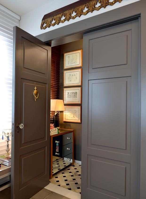 Hall de entrada | O espaço preserva o piso de mármore preto e branco original de 1952. A porta de madeira, cor Ponte Pênsil, da Suvinil, foi inspirada em uma semelhante vista pelos moradores na Itália (Foto: Marcelo Negromonte/Editora Globo)