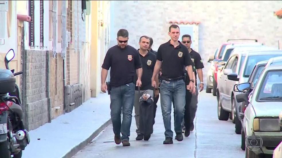 Agentes da PF saem com malote da casa de suspeito de incitar a morte de Bolsonaro — Foto: Reprodução/TV Globo