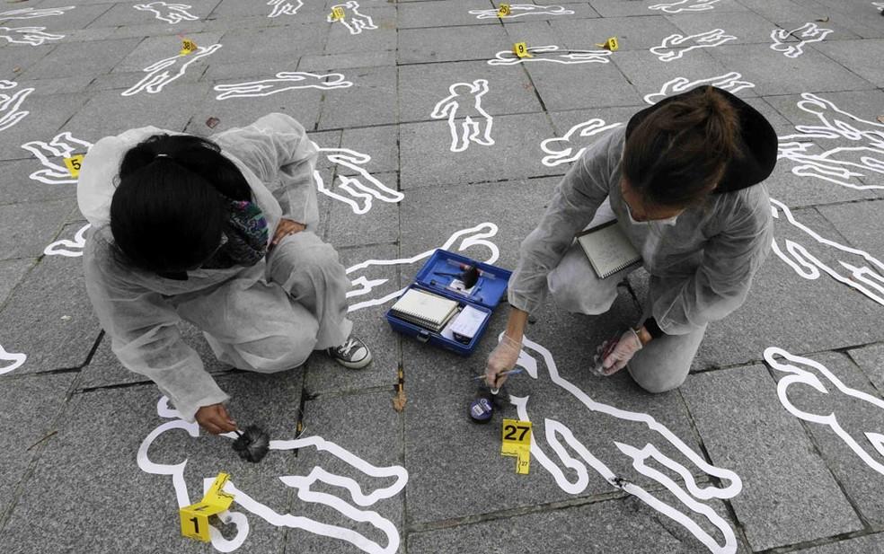 Membros da ONG francesa Ação contra a Fome fixam moldes simulando cenas de crime na praça Saint Sulpice, em Paris. O protesto chamou a atenção para as mortes por desnutrição ao redor do mundo. — Foto: Jacky Naegelen/Reuters