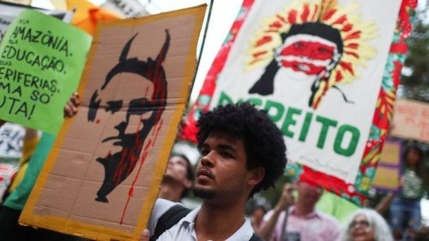 Manifestante no Rio de Janeiro exibe cartaz satirizando Bolsonaro; pauta ambiental deverá estar no discurso do presidente brasileiro na ONU (Foto: Reuters/Pilar Olivares via BBC Brasil)