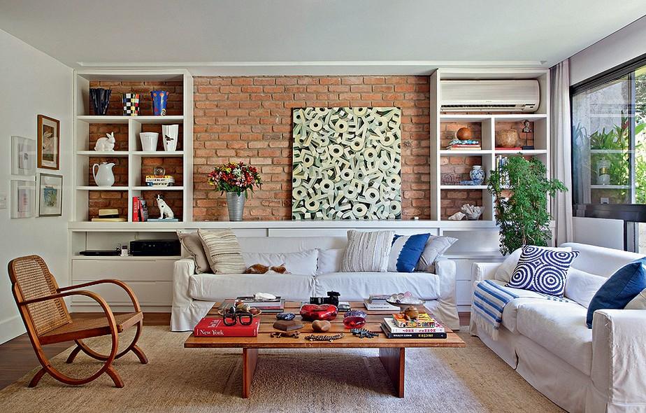 A sala de estar da apresentadora Patricya Travassos tem parede de tijolos e estante vazada. Sobre ela, fica apoiado o quadro da artista Cristina Tati
