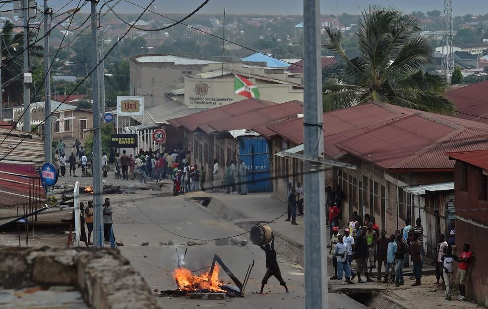 Manifestante contra o terceiro mandato do presidente do Burundi atira objetos sobre uma barricada em chamas no bairro Kinanira na capital Bujumbura (Foto: Carl de Souza/AFP)