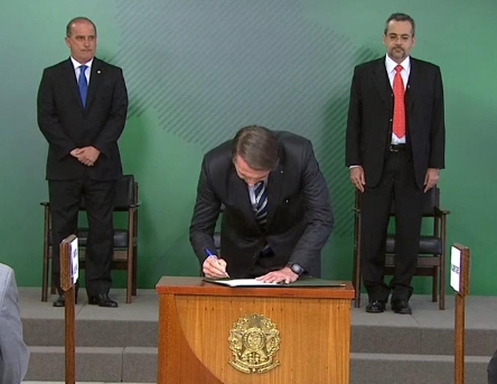 O presidente Jair Bolsonaro assina o termo de posse de Abraham Weintraub (de gravata vermelha) no Ministério da Educação — Foto: Reprodução/NBR