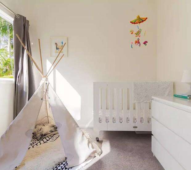 Os tons de branco e a cabana de brinquedo são destaques nesse quarto de bebê em Sydney, Austrália (Foto: Reprodução / Airbnb)