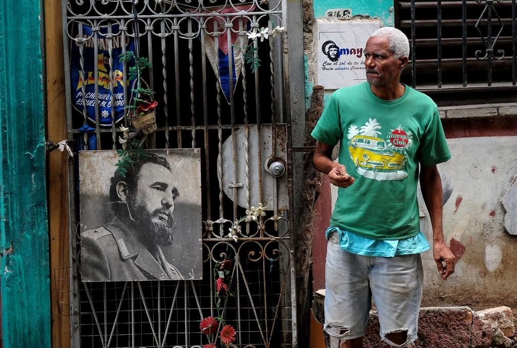 -  Homem em frente a um poster de Fidel Castro em Havana  Foto: Yamil Lage/AFP