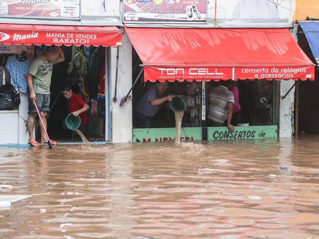 Populares tentam impedir a invasão da água depois da forte chuva que provocou diversos pontos de alagamento na Rua Padre Viegas de Menezes, no centro de Itaquera, na zona leste da capital paulista, na tarde desta quarta-feira (10). (Foto: WILLIAM VOLCOV/BRAZIL PHOTO PRESS/ESTADÃO CONTEÚDO)