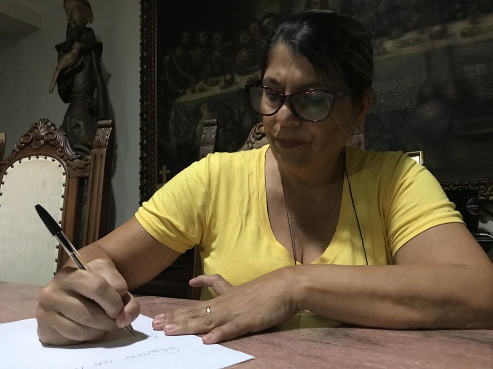 Durante a escrita, a administradora Sílvia dos Santros Silva segura caneta entre o segundo e terceiro dedo (Foto: Marília Marques/G1)