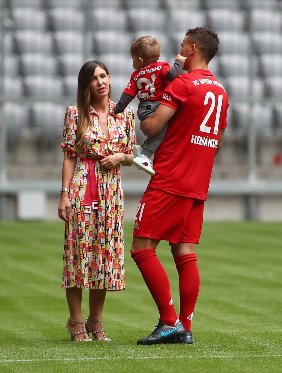 Lucas Hernández com o filho no colo e a esposa no gramado na apresentação como reforço do Bayern de Munique — Foto: REUTERS/Michael Dalder