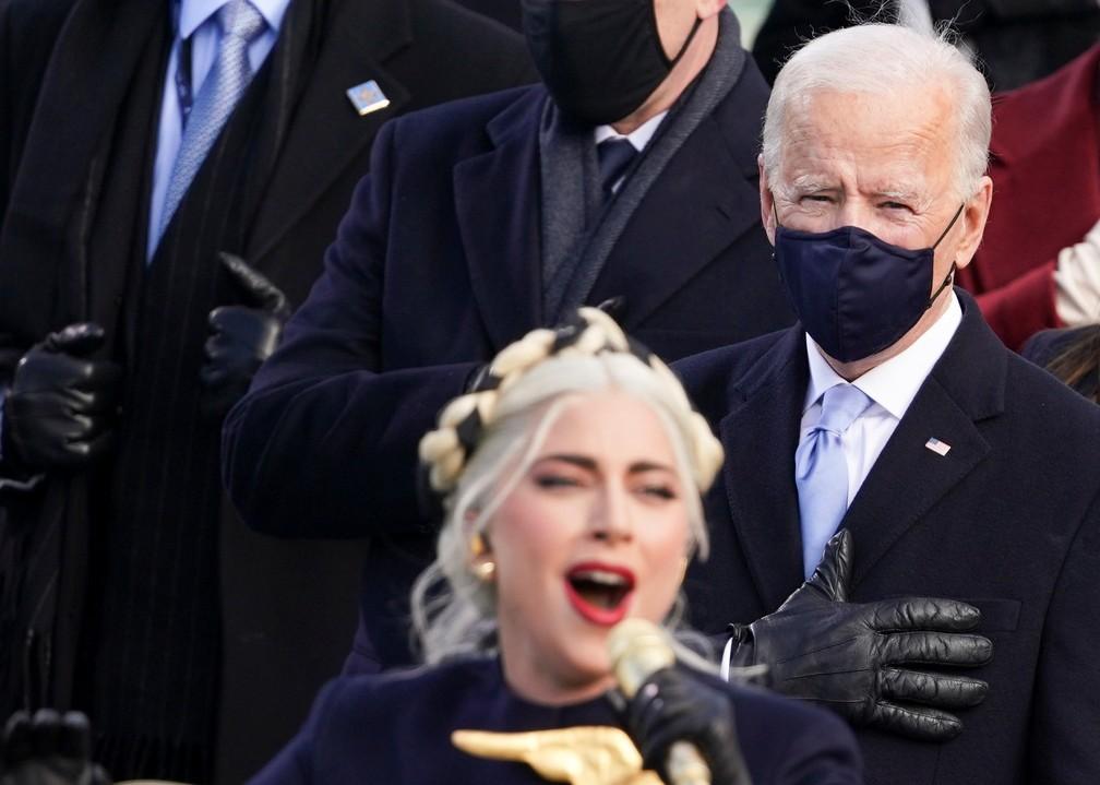 O presidente eleito dos EUA, Joe Biden, aparece ao fundo enquanto Lady Gaga canta o Hino Nacional durante a posse de Biden como 46º Presidente dos Estados Unidos na Frente Oeste do Capitólio dos EUA, em Washington, nesta quarta (20)   — Foto: Kevin Lamarque/Reuters