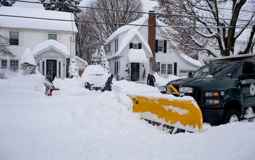Neve é removida da frente de casas em Binghamton, NY, na quinta-feira (17) — Foto: AP Photo/Craig Ruttle