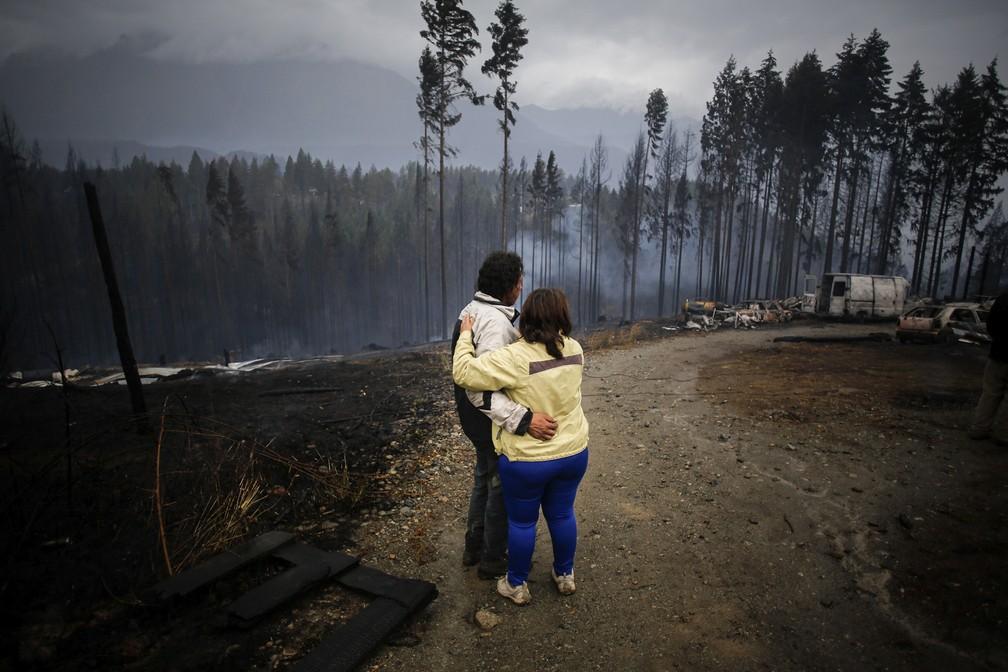Casal se abraça diante da fumaça deixada pelos incêndios que atingem florestas da Patagônia argentina — Foto: Matias Garay/AP Photo