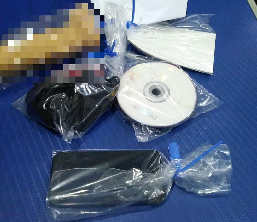 Celular com arquivos de pornografia infantil e outros objetos foram apreendidos pela polícia — Foto: G1 Santos