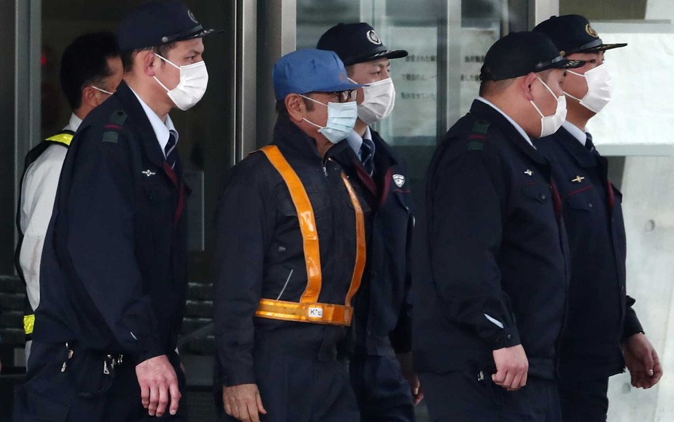 Brasileiro Carlos Ghosn (ao centro, de boné azul e máscara) é escoltado ao sair da Casa de Detenção de Tóquio — Foto: Behrouz Mehri / AFP Photo