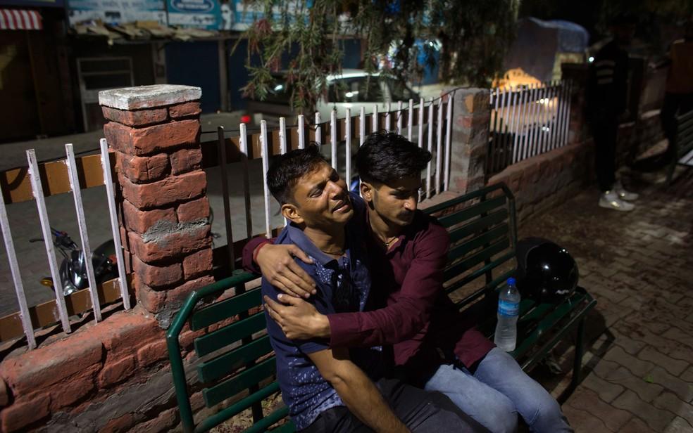 Pai chora e é consolado após saber da morte de seu filho em acidente com ônibus escolar a cerca de 60 km ao sul de Dharmsala, na Índia, na segunda-feira (9) (Foto: AP Photo/Ashwini Bhatia)