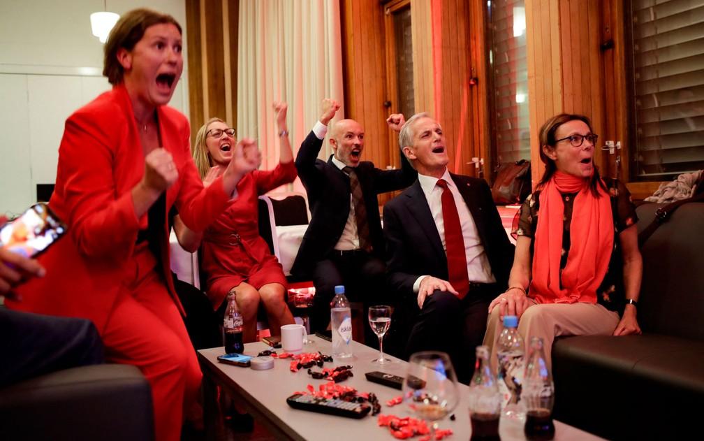 Membros do Partido Trabalhista da Noruega, entre eles o líder Jonas Gahr Støre (de gravata vermelha), comemoram o resultado das pesquisas de boca de urna das eleições parlamentares, em Oslo, na segunda-feira (13) — Foto: Javad Parsa/NTB/AFP