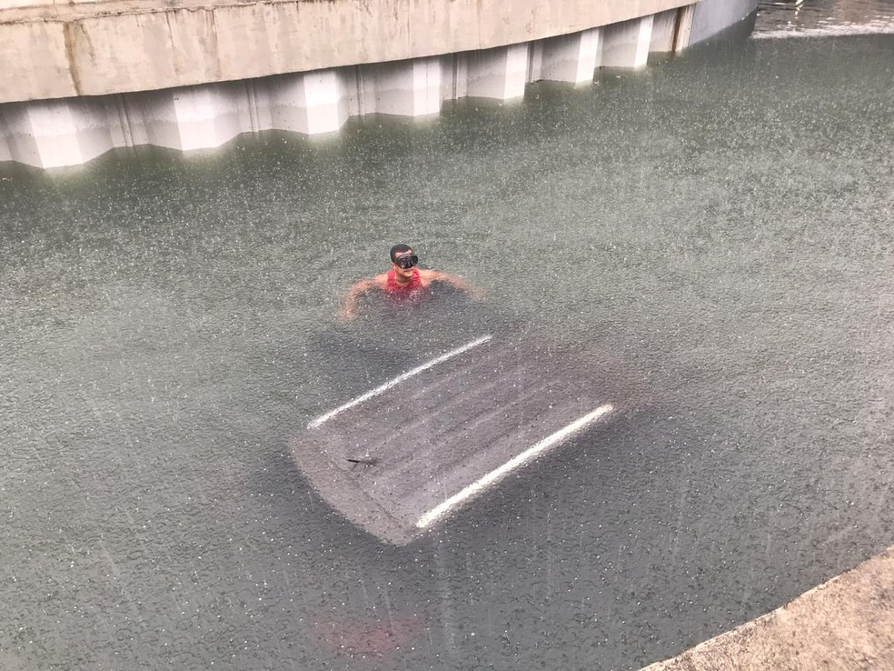 Bombeiro com máscara de mergulho se aproxima de carro submerso no mergulhão da Barra — Foto: Lívia Torres/TV Globo