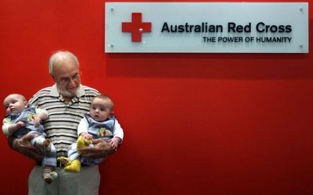 Segurando bebês cujas vidas ajudou a salvar, na Cruz Vermelha Australiana (Foto: Divulgação)
