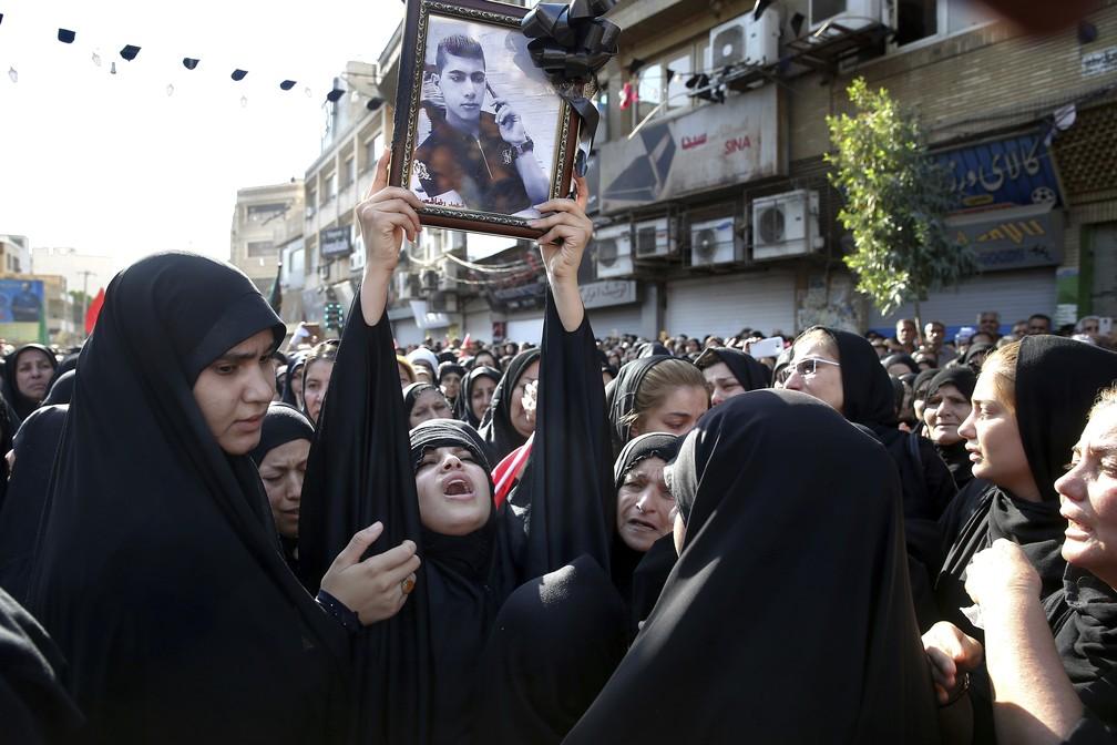 Familiares de vítima de ataque durante para militar carregam foto durante funeral em Ahvaz, no Irã — Foto: Ebrahim Noroozi/AP Photo