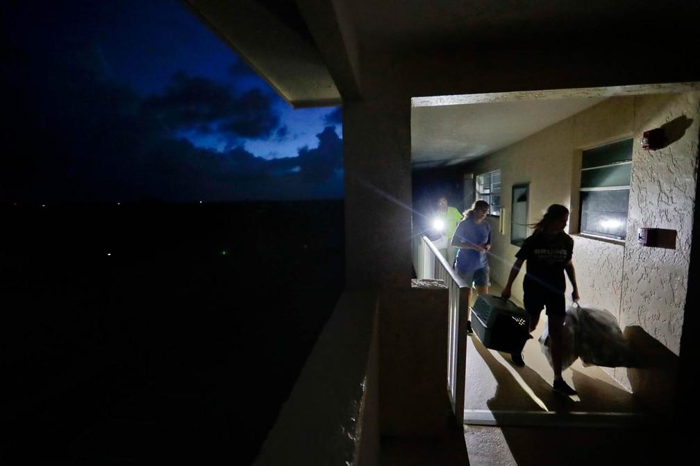 Família deixa apartamento que fica no 4º andar de um prédio de Marco Island, na Flórida, para retornar para a casa térea onde eles vivem, nesta segunda-feira (11). Joe Raymond, sua mulher e a filha se abrigaram na casa da mãe de Joe com medo da passagem do furacão Irma (Foto: David Goldman/AP)