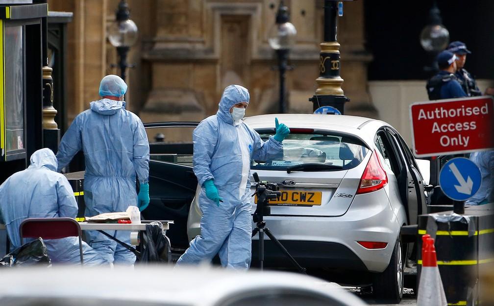 Investigadores forenses inspecionam carro de motorista que atropelou ciclistas e se chocou contra barreira de segurança do Parlamento britânico nesta terça-feira (14) em Londres (Foto: Henry Nicholls/Reuters)