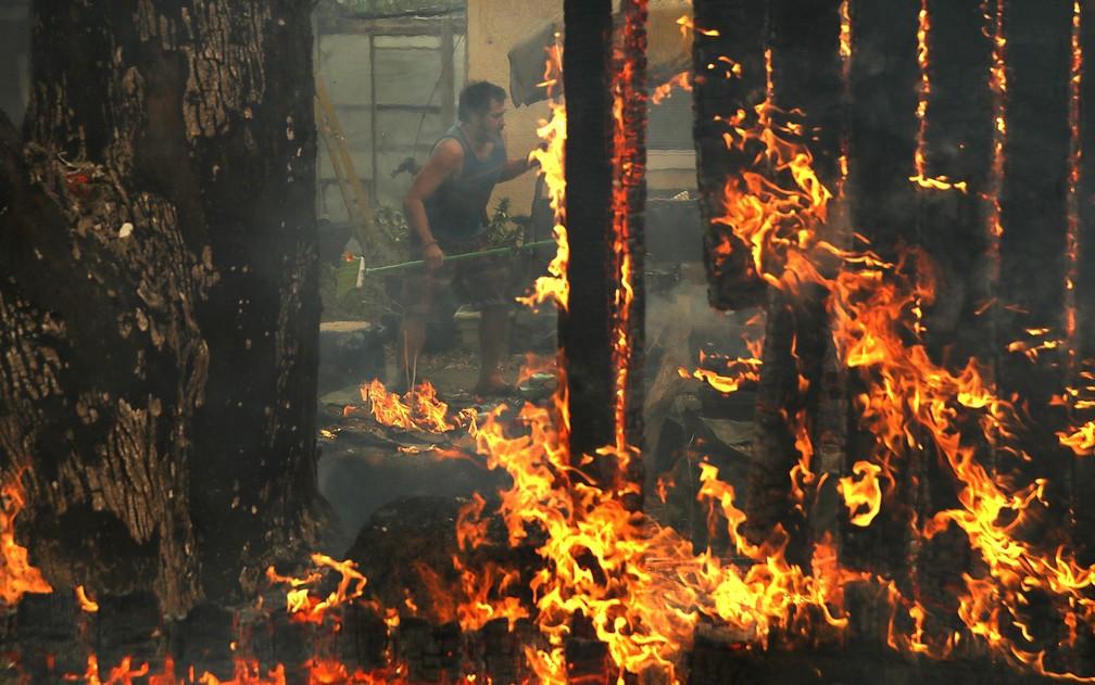 Morador corre para salvar pertences durante incêndio em sua casa em Glen Ellen, na Califórnia, na segunda-feira (9) (Foto: Justin Sullivan/Getty Images/AFP)