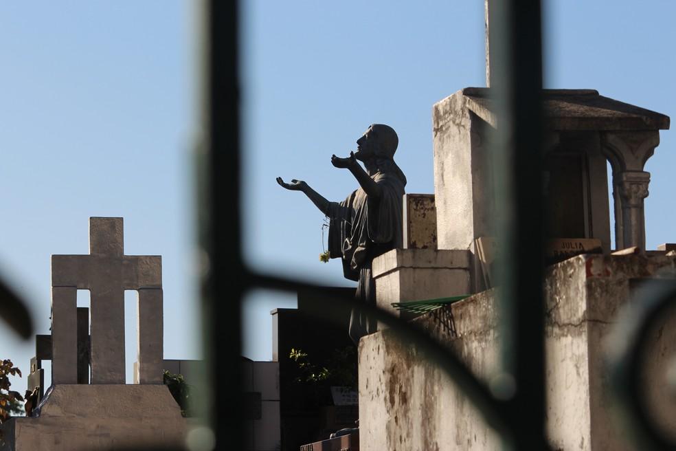 Em algumas cidades, parentes podem acompanhar de fora do cemitério o sepultamento — Foto: Carlos Dias/G1