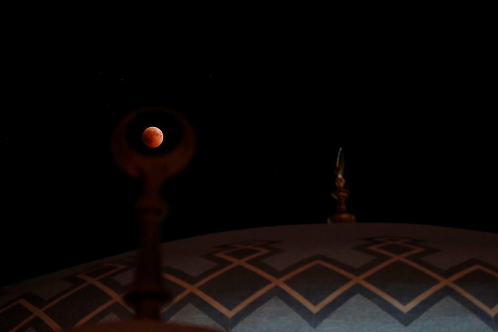 Lua vista durante o eclipse sobre a mesquita do Rei Abdullah, em Amã, na Jordânia (Foto: Muhammad Hamed/Reuters)